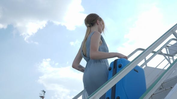 Cover Image for Young Woman in Dress with Travel Suitcase Rises by Staircase at Airport