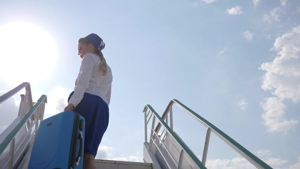 Thumbnail for Stewardess in Uniform Stands on Stairs of Plane Holds Suitcase and Passport with Air Ticket