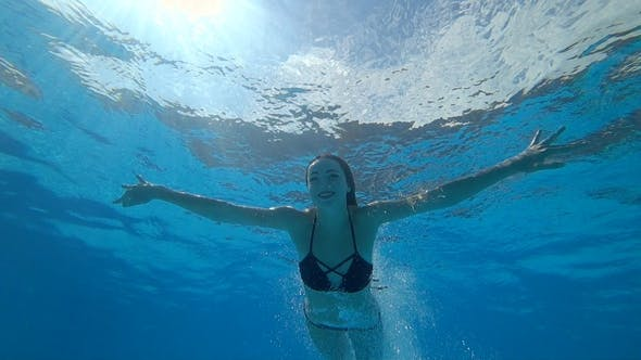 Cover Image for Beautiful Girl with Open Eyes Float Underwater at Clear Blue Swimming Pool