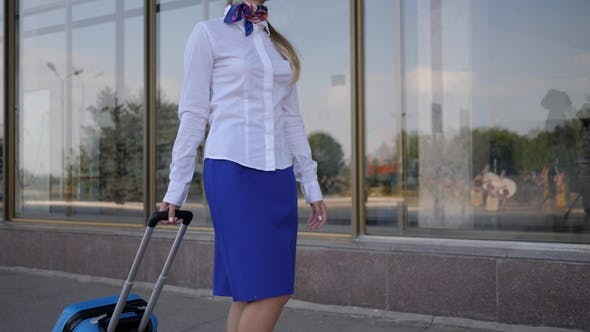 Thumbnail for Portrait Stewardess in Uniform Goes and Keeps Suitcase on Background Airport
