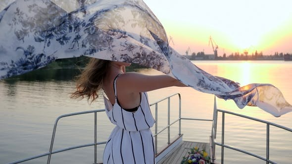 Cover Image for Smiling Girl Waving Cloth into Hand on Yacht in Summer Weekend in Sea on Sunset