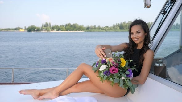 Cover Image for Young Woman Does Selfie on Yacht with Bunch of Bloom in Hands on Summer Rest