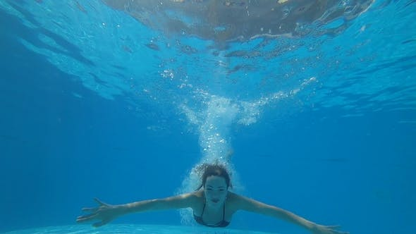 Cover Image for Happy Female with Open Eyes Swims Underwater in  at Summer on Background Bubbles