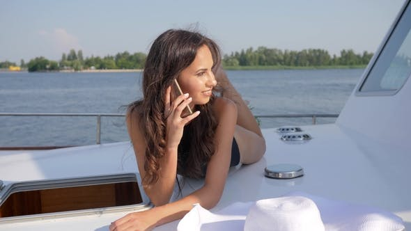 Thumbnail for Beautiful Girl Talking on Cell Phone Aboard Sailboat on River
