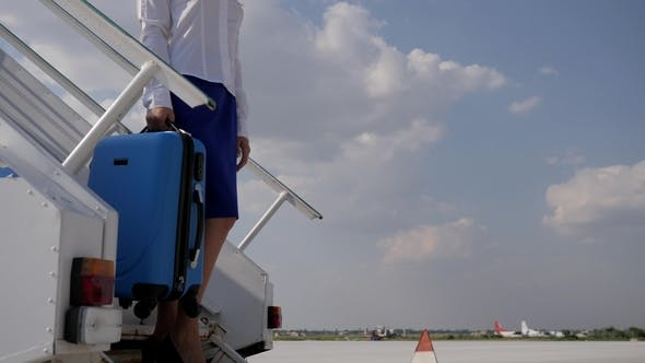 Thumbnail for Attractive Flight Attendant on Movable Staircase Keeps Travel Bag on Blue Sky Background