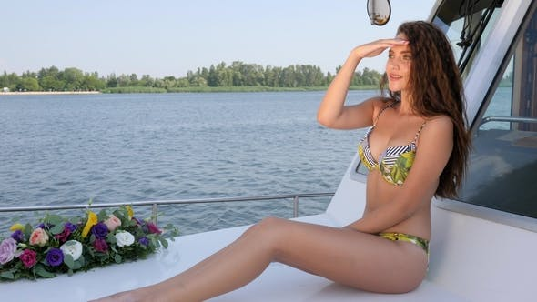 Cover Image for Young Female in Swimsuit Waving Hello and Looks into Distance on Sailboat in Summer