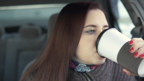 Thumbnail for Woman Drinks Coffee in Car