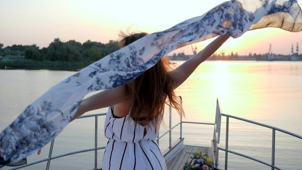 Thumbnail for Happy Girl Waving to Wind Standing on Aboard of Yacht in Sea on Background of Sunset