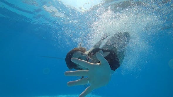 Thumbnail for Nice Female Swims Underwater with Open Eyes in Vibrant Environment on Background Bubbles