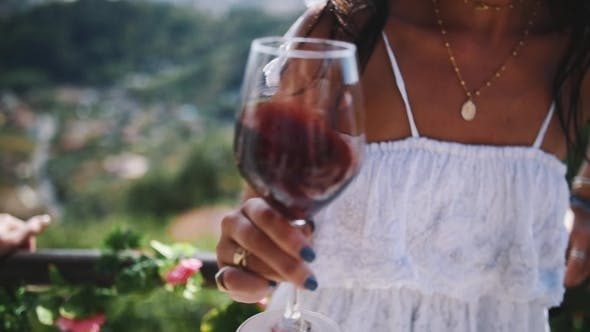 Thumbnail for Hand of Young Female Shakes Glass of Red Wine Outdoors