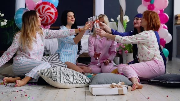Thumbnail for Bridesmaids Sitting in a Circle Bumping Glasses with Champagne Wishes and Say Happy