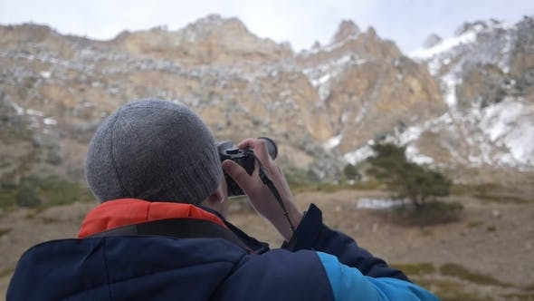 Thumbnail for Man Takes a Picture on a Camera in the Mountains