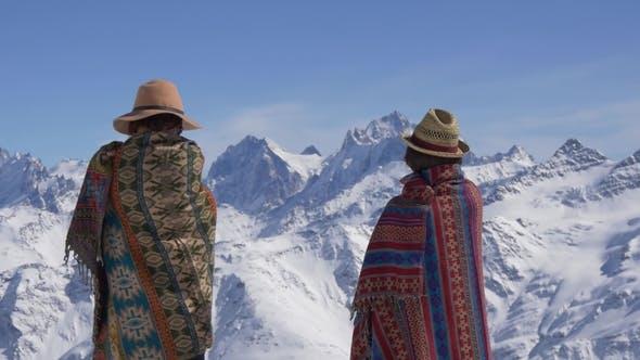 Thumbnail for Zwei Frauen in Wolldecken stehen und Blick auf die Berge