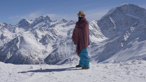 Thumbnail for Man in Funny Glasses in a Blanket at a Resort in the Mountains