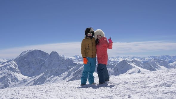 Thumbnail for Cheerful Guy with a Girl Posing in the Snowy Mountains