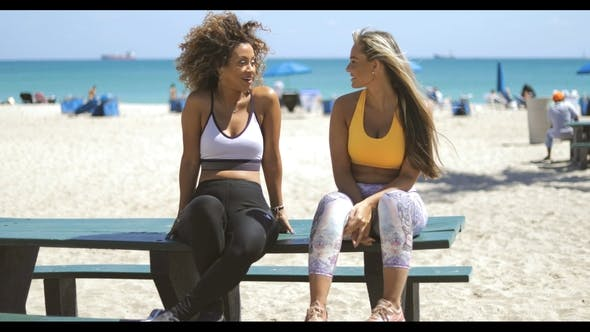 Thumbnail for Lounging Girlfriends in Sportswear on Beach