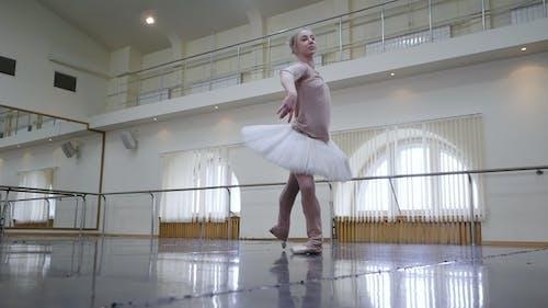 Ballerina in White Ballet Tutu Dress Practicing in Dance Studio or Gym. Woman Dancing Classical Pas