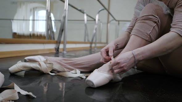 Thumbnail for Young Ballerina in Beige Costume Wraps White Silk Ribbons of Her Soft Top Ballet Shoes Pointe and