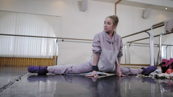 Ballerina Diligently Doing Stretching in a Ballet Class. Dancer Standing Warming Up Backstage Before