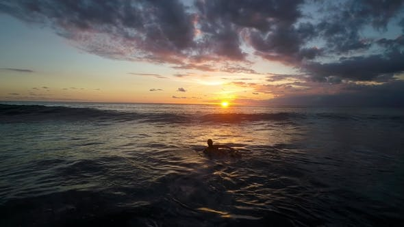 Thumbnail for Young Woman Paddling at Surfboard in Ocean