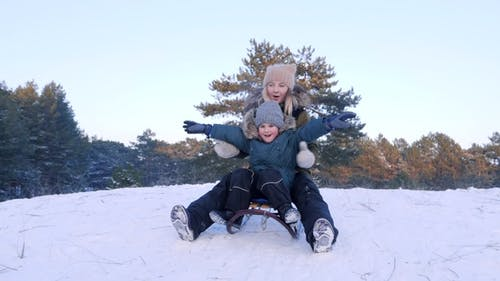 Young Mum with Son Sledding on Sunny Winter Day
