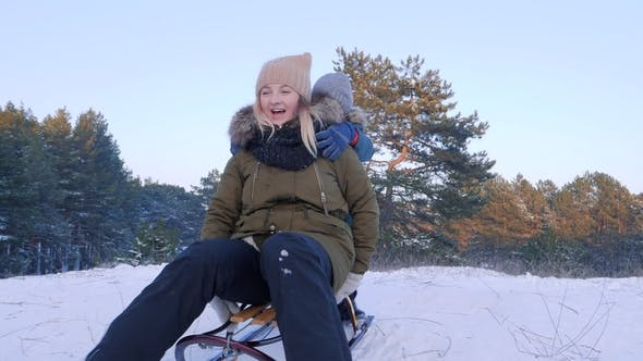 Thumbnail for Happy Mother and Son Ride in Sleigh on Snow in the Forest