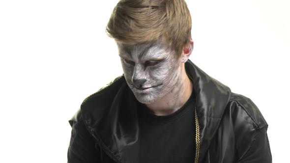 Body Art Raccoon on the Face of a Guy Who Turns His Head and Grins Proudly
