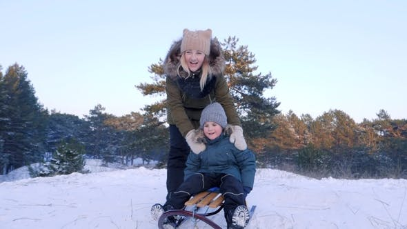 Thumbnail for Happy Young Woman Pushes Son on Sleigh from Snowy Hill and Runs after Him