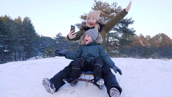 Thumbnail for Mom and Son on Sleigh on Snowy Hill Taking Pictures of Themselves Using Mobile Phone