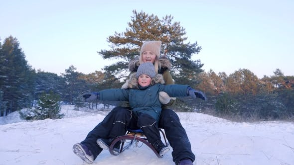 Thumbnail for Mother and Son Having Fun Sledging on Snow with Their Arms Raised in Forest