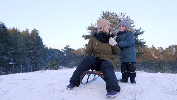 Thumbnail for Little Boy Pushes Mother on Sledge and She Rides from Snowy Hill in Winter Forest