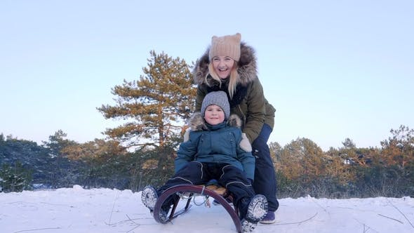 Cover Image for Mother Pushes Son on Sledge and He Rides from Snowy Hill in Winter Forest