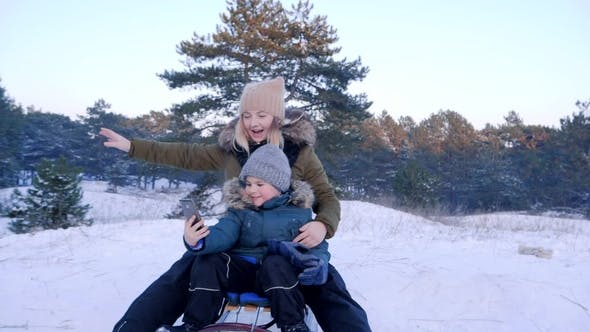 Thumbnail for Little Guy with Mobile Phone Shoots Video with Mom on a Sledge