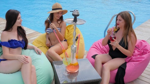 Thumbnail for Best Friends in Swimsuits Smoking Hookah and Drink Cocktails near Swimming Pool