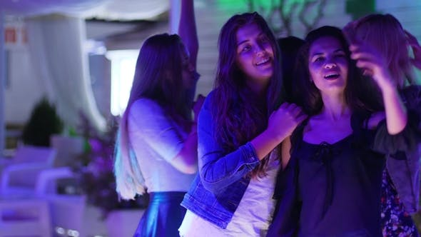 Cover Image for Selfie of Girlfriends at Disco Party on Background of Dancing People at Nightclub