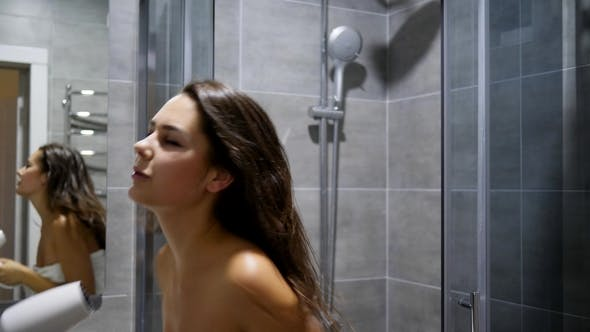 Thumbnail for Cheerful Brunette in Bath Towel Sings into Hairdryer as Microphone in Bathroom