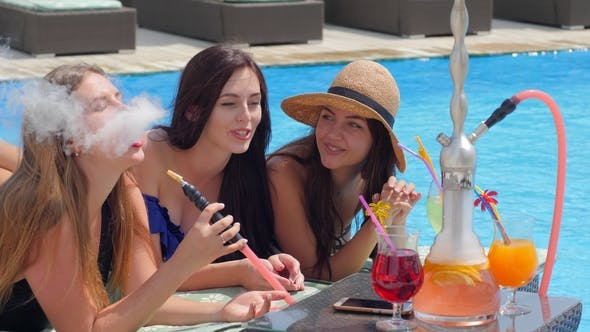 Thumbnail for Gossips Attractive Women with Colored Beverage Smoking Hookah near Pool on Summer Rest