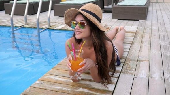 Thumbnail for Long-haired Female in Eyeglasses with Alcoholic Beverage Resting by Pool at Expensive Resort