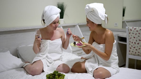 Cover Image for Cheerful Girlfriends in Bath Towels with Glasses in Hands Drink Champagne and Eat Cake in Bed