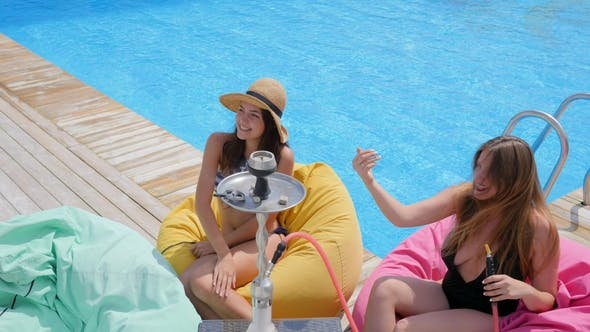 Thumbnail for Happy Youth in Swimsuits with Alcoholic Drinks in Arms Sitting and Smoking Hookah near Poolside