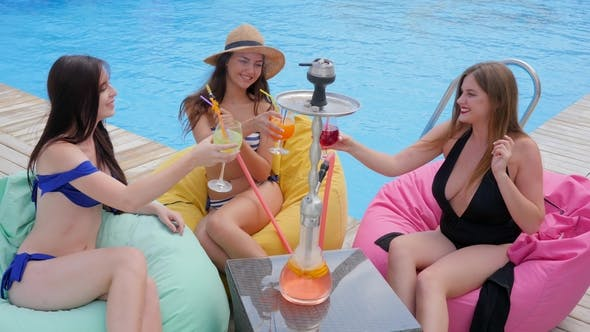 Thumbnail for Young Gossips Women Suits Smoking Hookah and Drink Cocktails on Pouf by Poolside on Summer Rest
