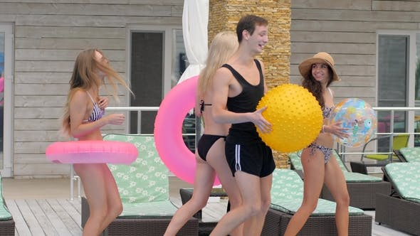 Thumbnail for Group of Young People in Swimsuits with Inflatable Ring on Holiday in Summer