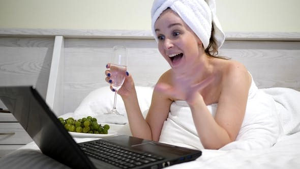 Thumbnail for Girl with Towel on Head with Champagne Communicating on Social Networks on Laptop at Bed