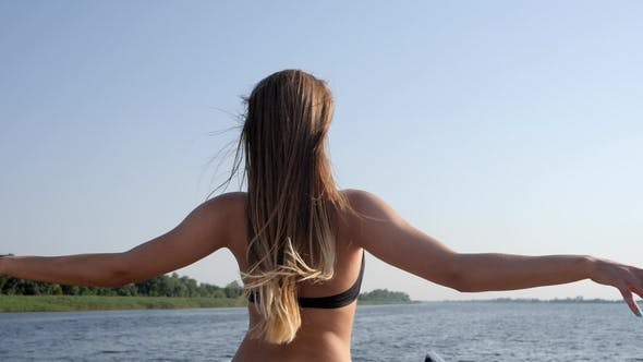 Thumbnail for Beautiful Female in Swimsuit Raises Hands and Enjoys Nature at River at Summer