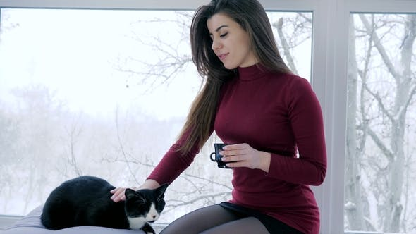 Cover Image for Young Woman Drinks Coffee and Strokes Cat Indoors