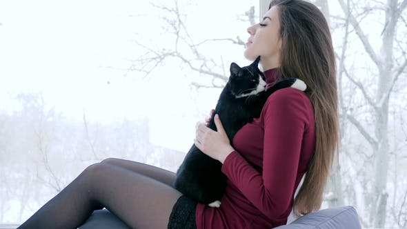 Thumbnail for Young Woman Spend Leisure with Favorite Pet Indoors on Background of Large Window
