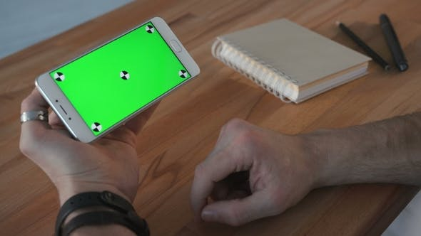 Thumbnail for Man Using Phone with Green Screen Display at Desk