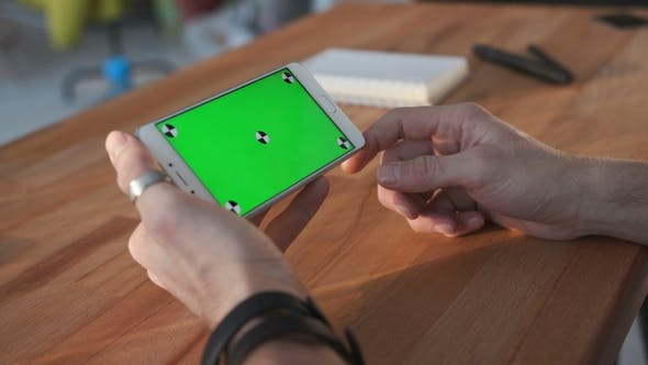 Thumbnail for Man Using Smartphone with Green Screen at Table