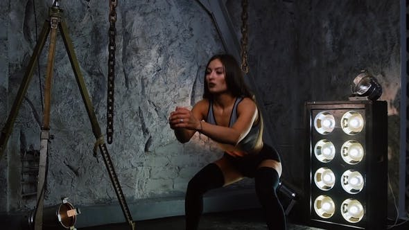 Thumbnail for Sexy Athletic Girl Performs Squats in Shorts in the Studio