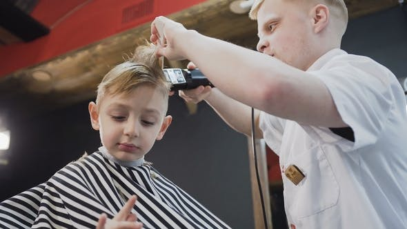 Cover Image for A Professional Hairdresser Makes a Stylish Hairstyle for a Beautiful Little Boy in the Barbershop